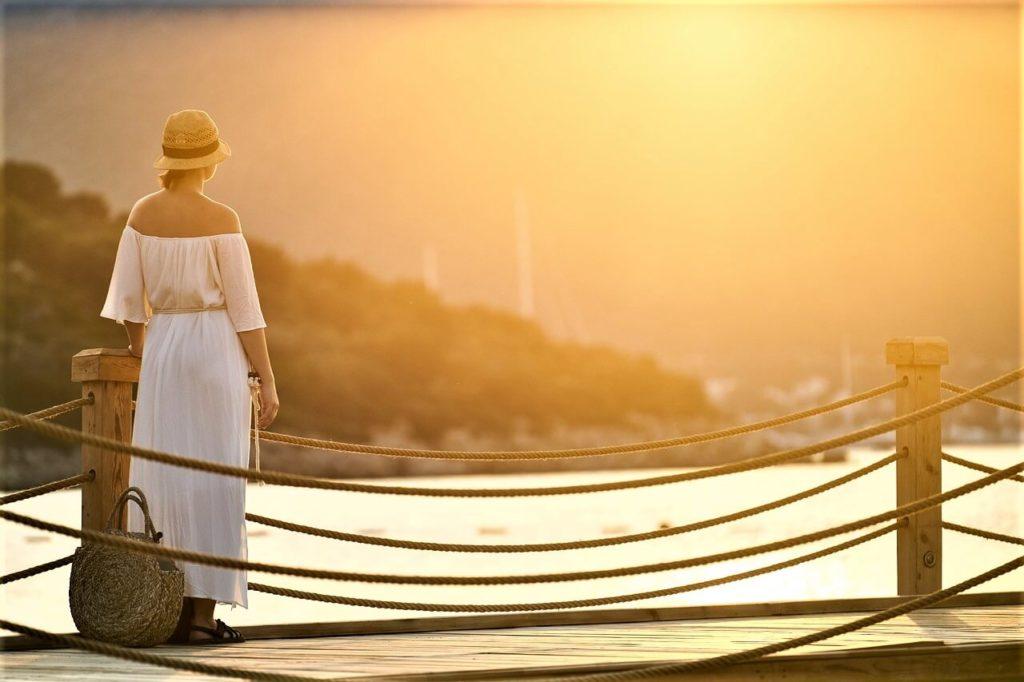 Žena v letních plážových šatech se západem slunce