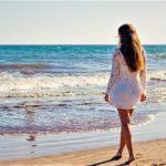 Žena v plážových šatech u moře