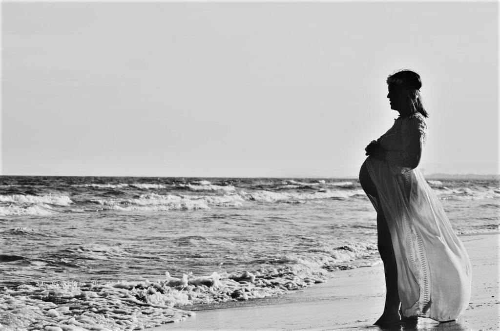 Těhotná žena v plážových šatech u moře